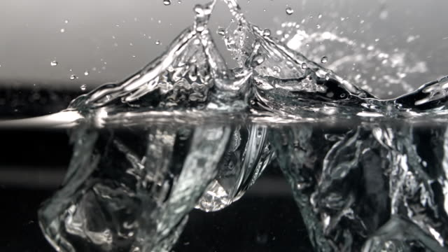 cu slo mo shot of ice cubes falling into water / seoul, south korea - ice cube stock videos & royalty-free footage