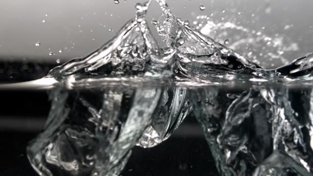 CU SLO MO Shot of ice cubes falling into water / Seoul, South Korea