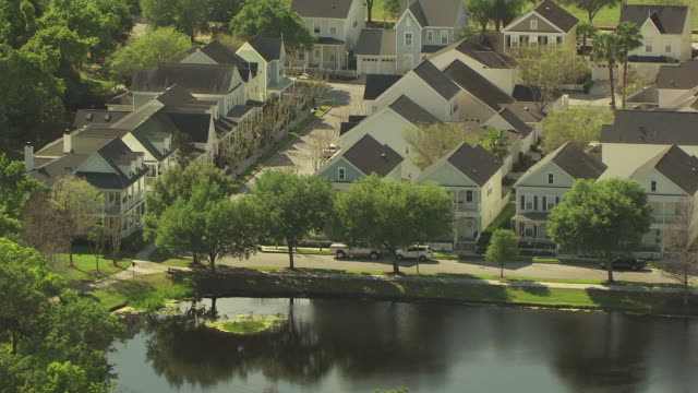 MS AERIAL Shot of identical houses and streets lined with cars around Lake Evelyn / Celebration, Florida, United States