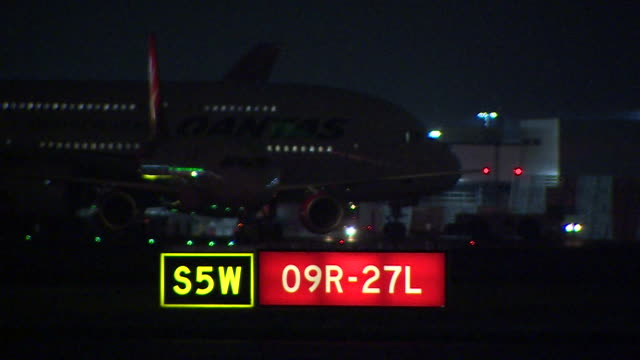 Shot of illuminated runway lights with a Qantas aircraft passing in the background at night at Heathrow Airport London