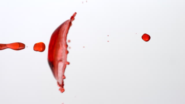 cu slo mo shot of impact showing two red drops coming together on white background / munich, bavaria, germany - impact stock videos and b-roll footage