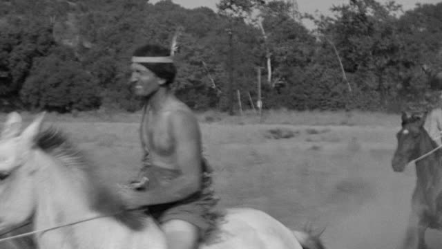 vídeos de stock e filmes b-roll de ms ts shot of indians on horseback riding through open field - índio americano