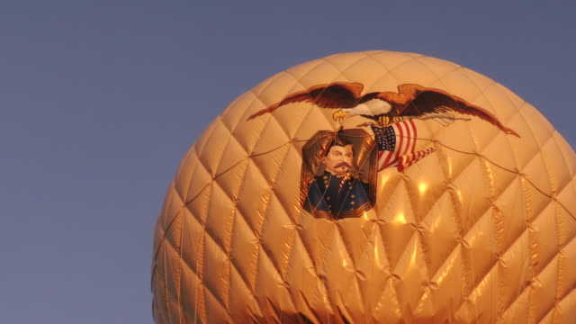 vídeos de stock e filmes b-roll de  cu shot of inflated hot air balloon painted with eagle american flag and image of union officer as it floats in air and two men in hot air balloon basket looking through binoculars / rochester, new york, united states - exército da união