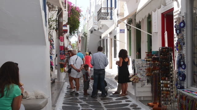 ms shot of island with shops and shoppers walking / mykonos, greece - mykonos stock videos and b-roll footage