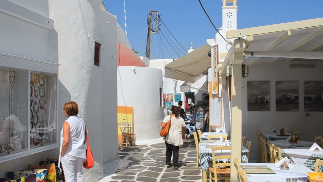 ms shot of island with shops and shoppers walking thru city and white buildings downtown / mykonos, greece - mykonos stock videos and b-roll footage
