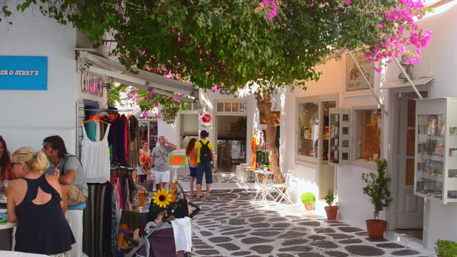 MS Shot of island with shops and shoppers walking thru city and white buildings downtown / Mykonos, Greece