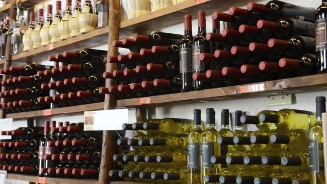 vidéos et rushes de ms shot of italian wine bottles at wine merchant / castellina in chianti, tuscany, italy - bouteille de vin