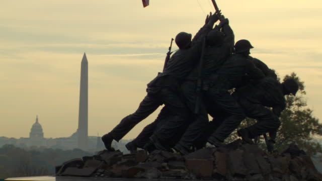 ms shot of iwo jima and marine corps war memorial in front side with washington monument and capitol building / washington, district of columbia, united states - 戦争記念碑点の映像素材/bロール