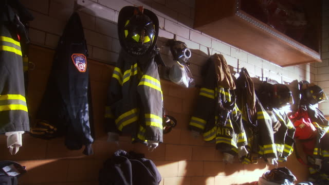 MS ZI Shot of jackets hanging on the wall in NYFD Engine Company 7 Ladder 1 fire house / New York, United States