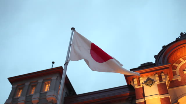 ms shot of japanese flag blowing by wind in front of tokyo station / osaka, kanto, japan - japan flag stock videos & royalty-free footage
