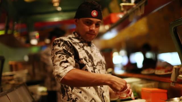 vídeos de stock, filmes e b-roll de ms shot of japanese restaurant in sao paulo, sushi prepared inside vw bus / sao paulo, brazil  - locais geográficos