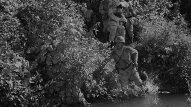 ms pan shot of japanese soldiers coming out from bushes and walking through stream - traditional helmet stock videos and b-roll footage