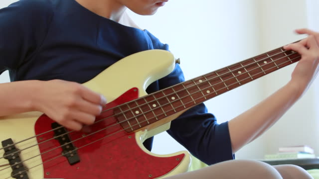 ms shot of japanese young woman playing bass guitar in her room / nakano, tokyo, japan - ギター点の映像素材/bロール