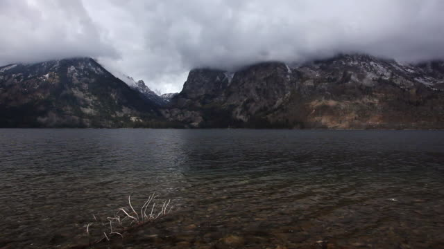 vídeos y material grabado en eventos de stock de ms shot of jenny lake with snow capped mountain range with storm clouds overhead, rocks below in water at grand teton national park / jackson hole, wyoming, united states - parque nacional de grand teton