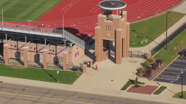 MS ZI AERIAL Shot of Jesse Owens statue with passersby and Jesse Owens Memorial Stadium at Ohio State University / Columbus, Ohio, United States