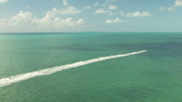 ms aerial zo ds shot of jet ski posse riding in water along pull out to posse riding along coast / key west, florida, united states - key west stock videos & royalty-free footage