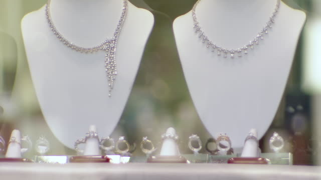CU Shot of jewelry on models in store window and people walking / Philadelphia, Pennsylvania, United States