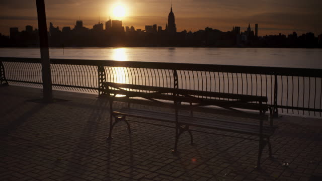 Shot of joggers running along the Hudson River silhouetted against the sunrise over the Manhattan Skyline
