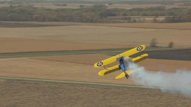 cu aerial ts shot of john mohr barnstormer flies sideways with smoke / minnesota, united states - biplane stock videos & royalty-free footage