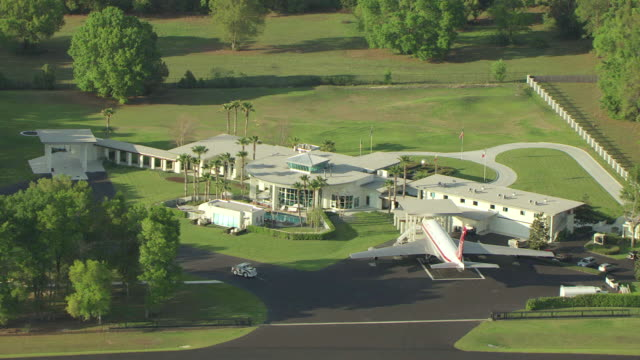 vidéos et rushes de ms aerial zo shot of john travolta house with airstrip in ground and neighboring houses / florida, united states - piste d'envol