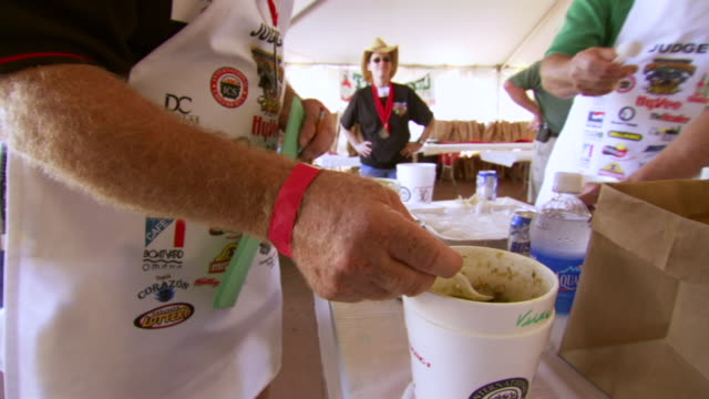 cu tu shot of judge taking sample from cup tastes it during worlds championship chili cook off / omaha, nebraska, united states - judge entertainment stock videos & royalty-free footage