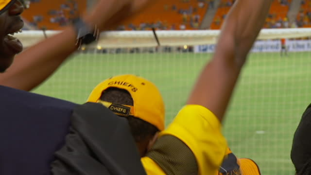cu shot of kaizer chiefs soccer spectators cheering / south africa - kleine personengruppe stock-videos und b-roll-filmmaterial