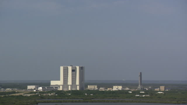 ws shot of kennedy space center vehicle assembly building and launch tower / cape canaveral, florida, united states - kennedy space center stock-videos und b-roll-filmmaterial
