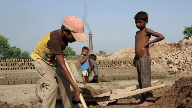 MS Shot of Kids working in handmade bricks factory / Old city of Lahore Punjab Pakistan