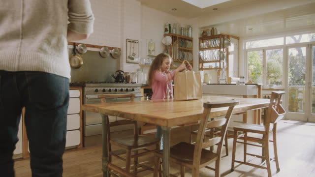 vídeos y material grabado en eventos de stock de ms shot of kitchen with dad and daughter enter with shopping then high fine / london, united kingdom  - bolsa de papel