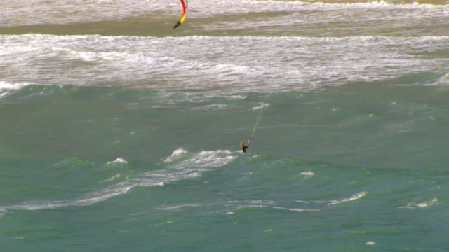 ms zi aerial shot of kite surfers with kites sailing waves in ocean / california, united states - kite sailing stock videos and b-roll footage