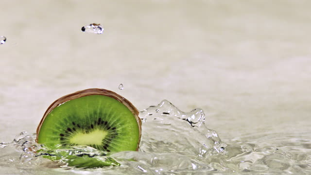 cu slo mo shot of kiwi fruits, actinidia chinensis, slice rolling on water and splashing / calvados, normandy, france - rolling stock videos & royalty-free footage