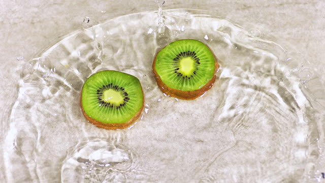 cu slo mo shot of kiwi fruits, actinidia chinensis, slice rolling on water and splashing / calvados, normandy, france - calvados stock-videos und b-roll-filmmaterial