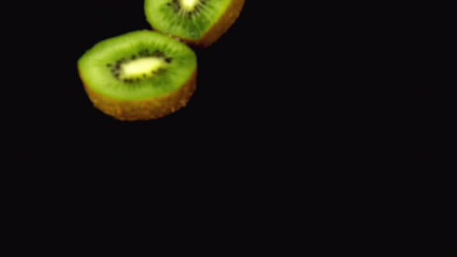 cu slo mo shot of kiwi fruits, actinidia chinensis, slice rolling on water and splashing / calvados, normandy, france - calvados stock videos and b-roll footage