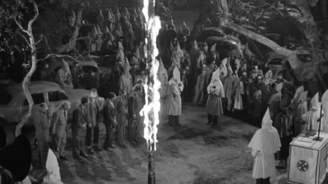 ws shot of  klan rally, burning a cross with some peoples standing around  - ku klux klan stock videos and b-roll footage