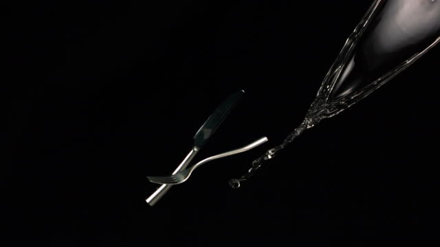 MS SLO MO Shot of Knife,fork,water and ice fly through air / Toronto, Ontario, Canada