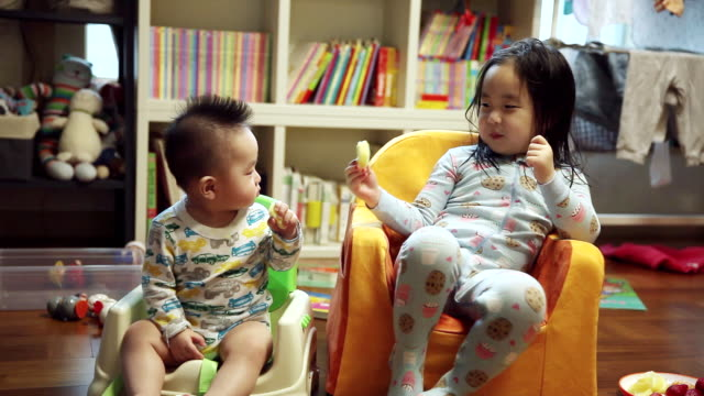 ms shot of korean brother and sister sitting on small chair / jeju, jeju-do, south korea  - small stock videos & royalty-free footage