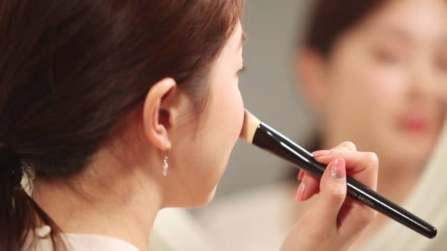 CU Shot of Korean woman applying make up with blush in mirror / Seoul, South Korea