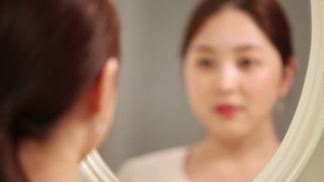 cu r/f shot of korean woman applying make up with blush in the mirror / seoul, south korea  - メイクアップブラシ点の映像素材/bロール