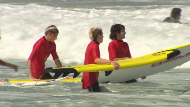 MS Shot of ladies enjoying and surfing in sea / Biarritz, France