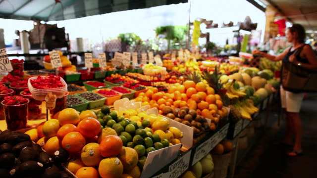 vidéos et rushes de ms pan shot of lady shopping at french fruit and vegetable stand in atwater market / montreal, quebec, canada - marché paysan
