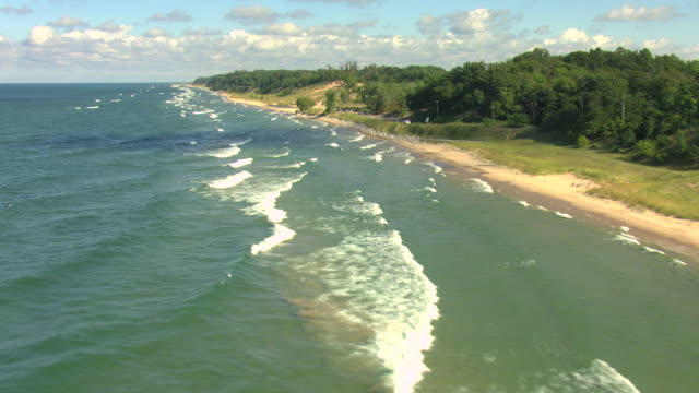 vídeos de stock, filmes e b-roll de ms aerial shot of lake michigan coastline with waves and beach with inland forest in muskegon county / michigan, united state - lago michigan
