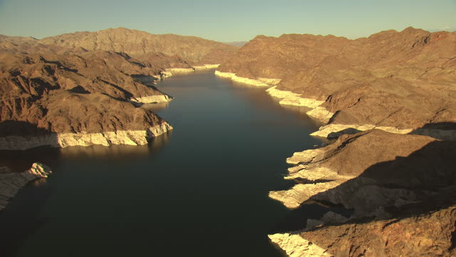 ms aerial shot of lake with water history lines on surrounding rocky mountains with morning sunshine / lake mead, nevada, united states - sunshine lake bildbanksvideor och videomaterial från bakom kulisserna