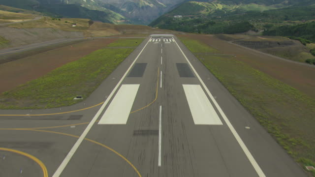 WS TU AERIAL Shot of landing strip as ascend and mountains with clouds in sky / Telluride, Colorado, United States