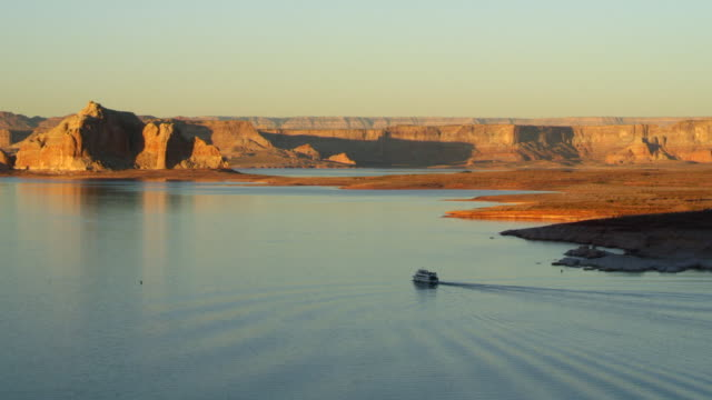 ws shot of large boat gliding through lake powell with multi-colored plateaus during sunset / glen canyon national rec area, arizona, united states - lake powell stock videos and b-roll footage