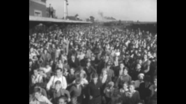 vídeos de stock e filmes b-roll de shot of large crowd behind train carrying republican presidential candidate alf landon / landon on back of train waving at crowd / two shots of... - partido republicano americano