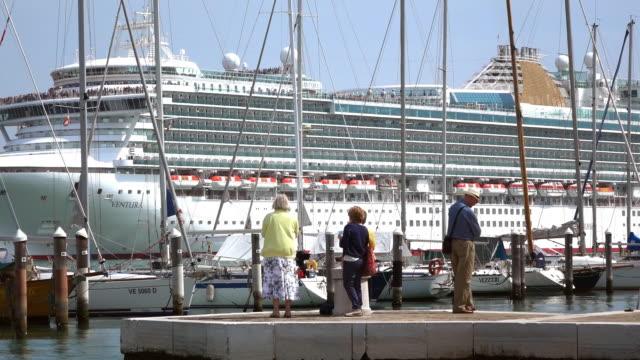 vídeos de stock e filmes b-roll de ms shot of large cruise ship and people standing near harbor at canale di san marco / venice, veneto, italy - navio de passageiros