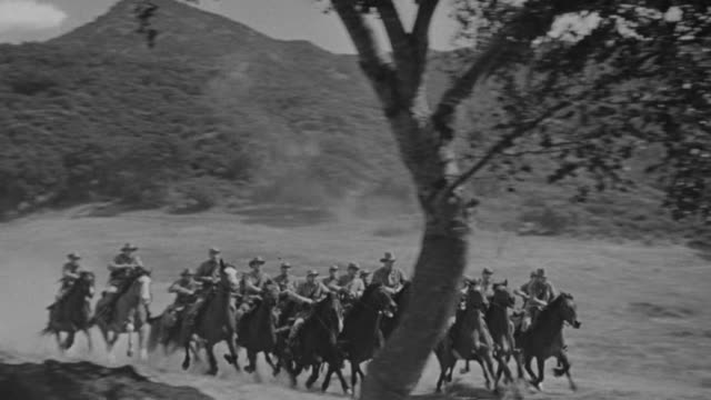 WS TS Shot of large group of men (cavalry) riding through open field on horseback.