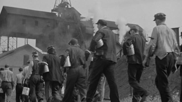 ms shot of large group of mine workers walking onto job site - bombola video stock e b–roll