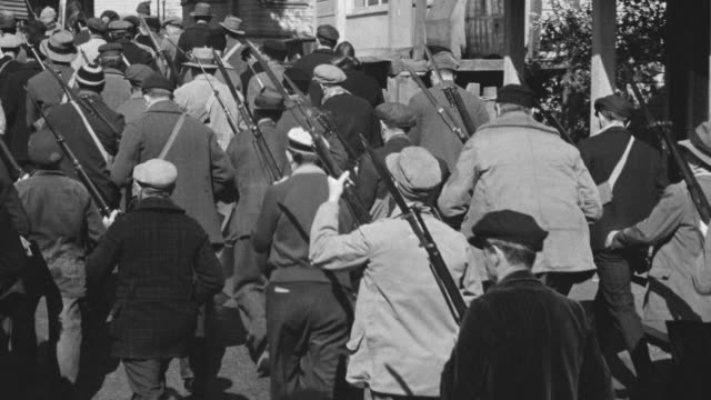 MS POV Shot of large mob of Nazi soldiers carrying guns marching through town