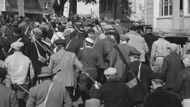 ms pov shot of large mob of nazi soldiers carrying guns marching through town  - mob stock-videos und b-roll-filmmaterial